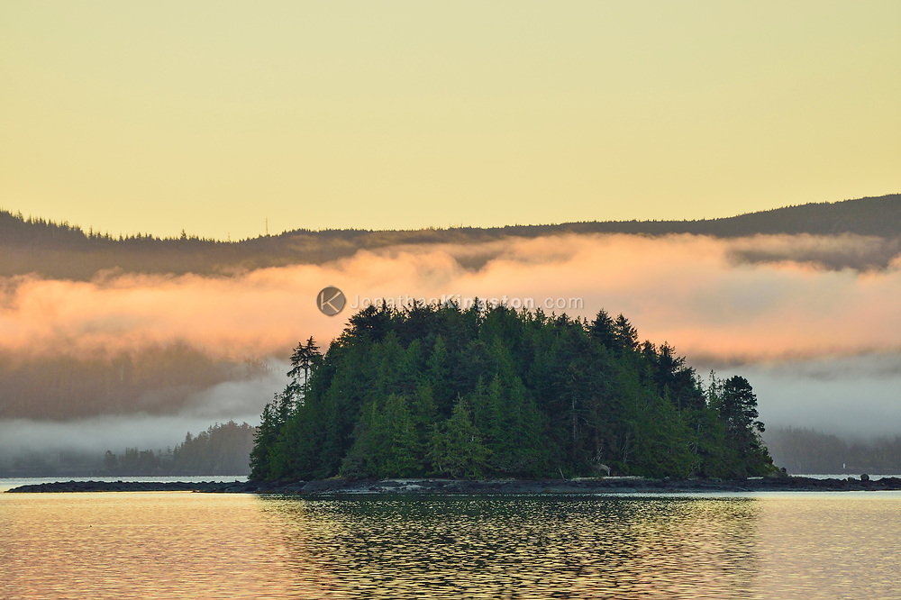 Dawns light illuminates clouds over the bay in front of Queen Charlotte City, Haida Gwaii, British Columbia.