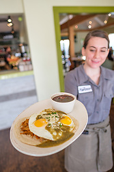 Waitress holding plate of ranchero green eggs and ham at Righteous Foods, Fort Worth, Texas, USA.