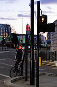 The face of a cyclist is illuminated from the red traffic light during evening rush-hour traffic, on 26th February 2021, in London, England.