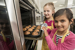 Schoolgirls removing muffins from oven in home economics class, Bavaria, Germany
