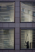 A workman wipes the ceiling of a vacant office building in the City of London. Reaching high above his head, the man uses a squeegee-type mop to clean the shiny surfaces of the ceiling and light fittings before the completion of these new corporate floors, currently unoccupied by the tenant or owner and with fixtures, fittings and furnishings still to be fitted by the property's management. Work has yet to be completed before the hundreds or thousands of employees can move in to this building in the heart of the UK capital's financial district, founded by the Romans in AD43.