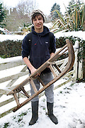 Model released portrait of teenage boy in the snow holding a wooden sledge, Suffolk, England