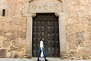 Stylish young local woman carrying plastic carrier bag and strolling in old town of Avila, Spain