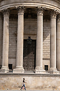 A woman walks beneath the pillars and column architecture of Sir Christopher Wren's St Paul's Cathedral south transept, on 24th June 2021, in London, England. CREDIT RICHARD BAKER.