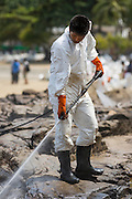 02 AUGUST 2013 - KOH SAMET, RAYONG, THAILAND: A worker uses a high pressure hose to apply dispersant and water to an oil spill on Ao Prao Beach on Koh Samet island. About 50,000 liters of crude oil poured out of a pipeline in the Gulf of Thailand over the weekend authorities said. The oil made landfall on the white sand beaches of Ao Prao, on Koh Samet, a popular tourist destination in Rayong province about 2.5 hours southeast of Bangkok. Workers from PTT Global, owner of the pipeline, up to 500 Thai military personnel and volunteers are cleaning up the beaches. Tourists staying near the spill, which fouled Ao Prao beach, were evacuated to hotels on the east side of the island, which was not impacted by the spill. Officials have not said when Ao Prao beach would reopen. PTT Global Chemical Pcl is part of state-controlled PTT Pcl, Thailand's biggest energy firm.    PHOTO BY JACK KURTZ