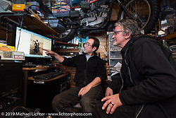 Keiji Kawakita showing photos of his Harley racing father back in the day to Harley-Davidson head of design Ray Drea in Keiji's office at Hot Dock Custom Cycles. Japan. Wednesday, December 10, 2014. Photograph ©2014 Michael Lichter.