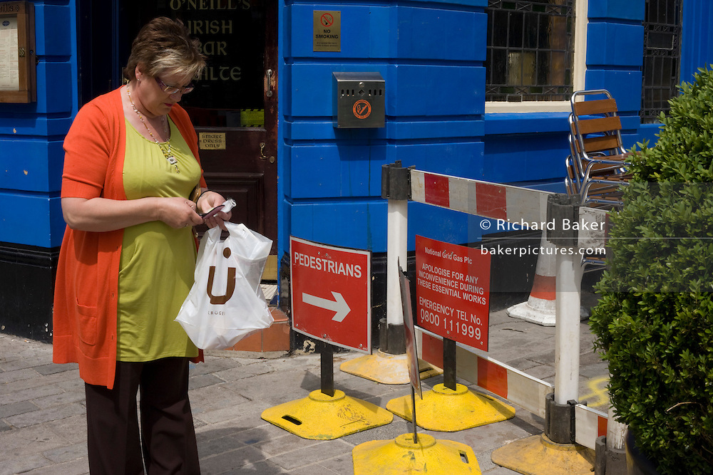 Typing a text message with a mobile phone near pavement repairs in the City of London