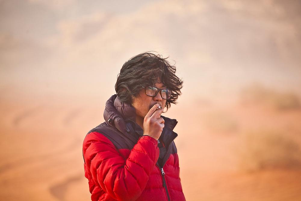 SeongRyeong Bak walks smoking a cigarette through the red sand desert of Wadi Rum, Jordan