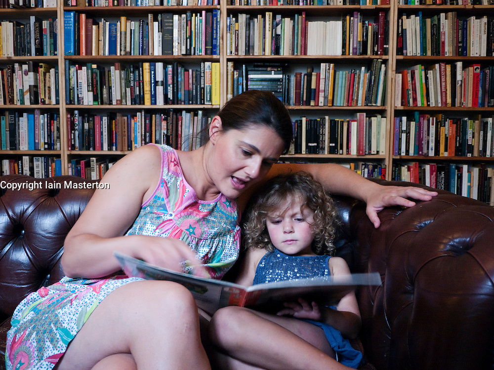 Woman reading to young girl in a bookshop in Berlin