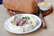 Labneh (Lebanese yogurt cheese made from cows milk) served with olive oil, onion and bread and butter