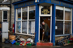 © Licensed to London News Pictures. 29/12/2015. York, UK. Ruined stock and belongings lie on the street  CHAZ BURNS sweeps out the front door of his fishing tackle shop,  which was badly damaged by flood waters, on Huntington Road in York. Further rainfall is expected over coming days as Storm Frank approaches the east coast of the country. Photo credit: Ben Cawthra/LNP