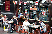 People having a drink outside a tourist pub in central London. This is the sort of pub that is more for tourists than locals, offering such things as 'classic pub drinks' and covered in St George's flags.