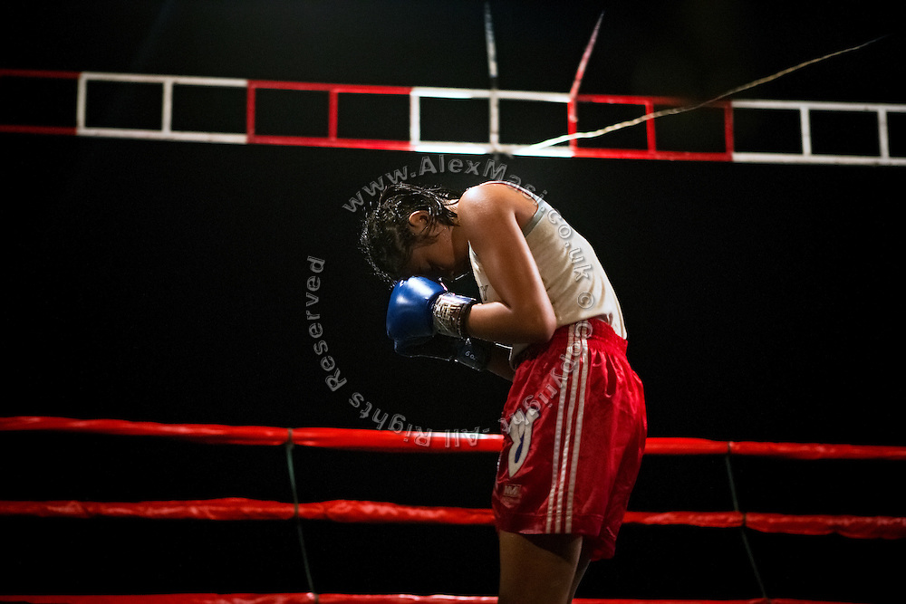 An adolescent girl is praying before the start of a Muay Thai boxing match, organised in a village near Ubon Ratchathani, northeast Thailand.