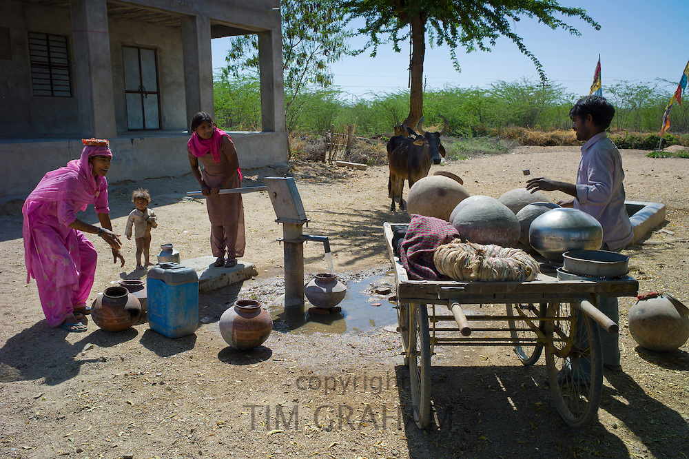 Indian women in sari fetching water pot from well at Jawali village in Rajasthan, Northern India