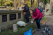Two women take care of a grave with flowers and candles in Rakowicki cemetery in Krakow, Poland in 2019.