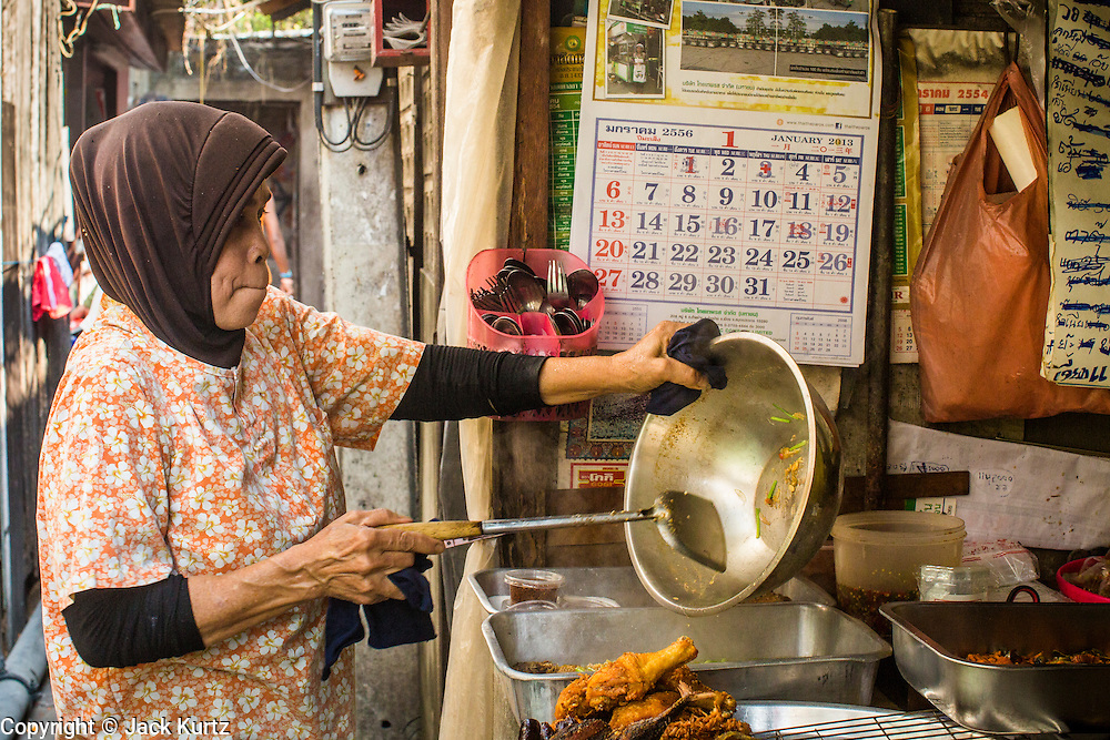 """10 JANUARY 2013 - BANGKOK, THAILAND:  A Muslim woman prepares food at the lunch stand in front of her home in the Baan Krua neighborhood in Bangkok. The Ban Krua neighborhood of Bangkok is the oldest Muslim community in Bangkok. Ban Krua was originally settled by Cham Muslims from Cambodia and Vietnam who fought on the side of the Thai King Rama I. They were given a royal grant of land east of what was then the Thai capitol at the end of the 18th century in return for their military service. The Cham Muslims were originally weavers and what is known as """"Thai Silk"""" was developed by the people in Ban Krua. Several families in the neighborhood still weave in their homes.   PHOTO BY JACK KURTZ"""