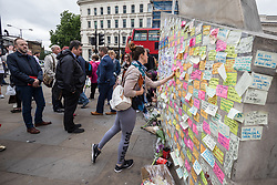 © Licensed to London News Pictures. 08/06/2017. London, UK. A woman sticks a message of support to a wall at London Bridge where eight people lost their lives in a terrorist attack on the evening of Saturday 3 June 2017. Photo credit: Rob Pinney/LNP