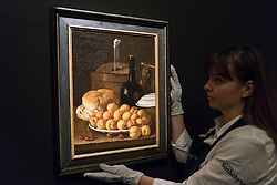 "© Licensed to London News Pictures. 29/11/2019. LONDON, UK. A technician presents ""Still life with a plate of apricots, cherries, bread, wine cooler and receptacles"", 1765, by Luis Mendelez (Est. GBP600-800k) at the preview of Old Masters sales at Sotheby's, New Bond Street.  Works will be offered for sale on 4 and 5 December.  Photo credit: Stephen Chung/LNP"