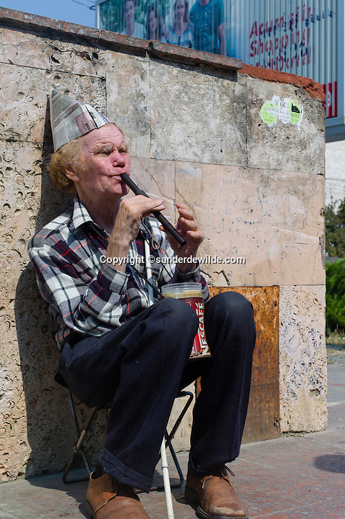 Moldova Chisinau Blind man plays the flute at the entrance of the underground crossing with a paperhat, to earn some money to be put in his nescafe jar.