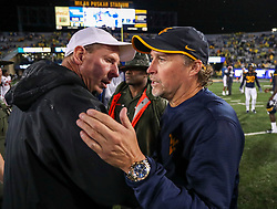 Sep 8, 2018; Morgantown, WV, USA; West Virginia Mountaineers head coach Dana Holgorsen talks with Youngstown State Penguins head coach Bo Pelini after the game at Mountaineer Field at Milan Puskar Stadium. Mandatory Credit: Ben Queen-USA TODAY Sports