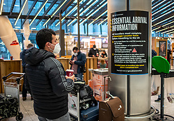 © Licensed to London News Pictures. 15/02/2021. London, UK. A Passenger walks past a Covid-19 government poster reminding people to fill out their Passenger Locator Form for people arriving from red-list countries at London Heathrow Terminal 5 this morning as hotels near Heathrow start to accept quarantine passengers. From today, (Monday 15 February 2021) anyone arriving from a red-list destination must quarantine at a designated hotel and pay a hotel fee of £1,750 for a 10 day quarantine period. Photo credit: Alex Lentati/LNP