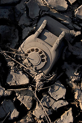 30 Sept, 2005. New Orleans, Louisiana. Lower 9th ward. Hurricane Katrina aftermath.<br /> The remnants of the lives of ordinary folks, now covered in mud as the flood waters remain. a telephone lies stuck in the mud.<br /> Photo; ©Charlie Varley/varleypix.com