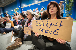 13 December 2019, Madrid, Spain: A woman holds a sign reading 'Safe and Just Article 6', as people gather for a sit-in demonstration at COP25, to claim space for a range a groups whose voices are not often listened to in the space of global climate negotiations: youth, women, frontline communities, indigenous communities.