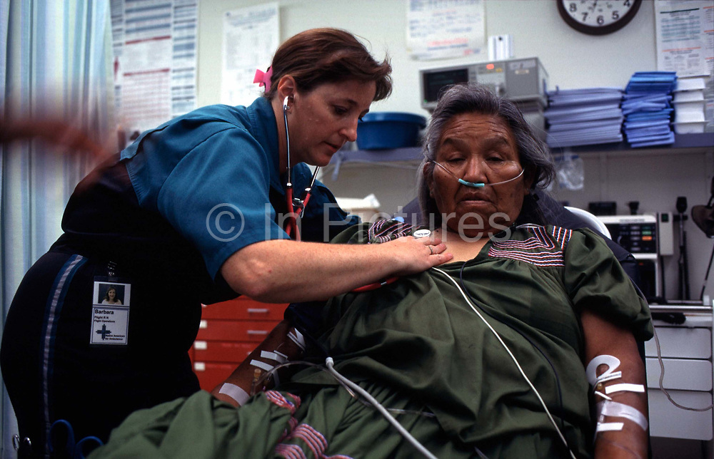 """A flight nurse examines a lady from the Native American Reserve at San Carlos, Arizona, from where she is to be taken from the rural Arizona airstrip by  twin-propeller powered aircraft, an air ambulance, to hospital for treatment. The San Carlos Apache Indian Reservation, in southeastern Arizona, United States, was established in 1872 as a reservation for the Chiricahua Apache tribe. It was referred to by some as """"Hell's Forty Acres,"""" due to a myriad of dismal health and environmental conditions. The San Carlos Reservation is one of the poorest Native American communities in the United States, with an annual median household income of approximately $14,000 in 2000, according to the US Census. About 60% of the people live under the poverty line, and 68% of the active labor force is unemployed"""