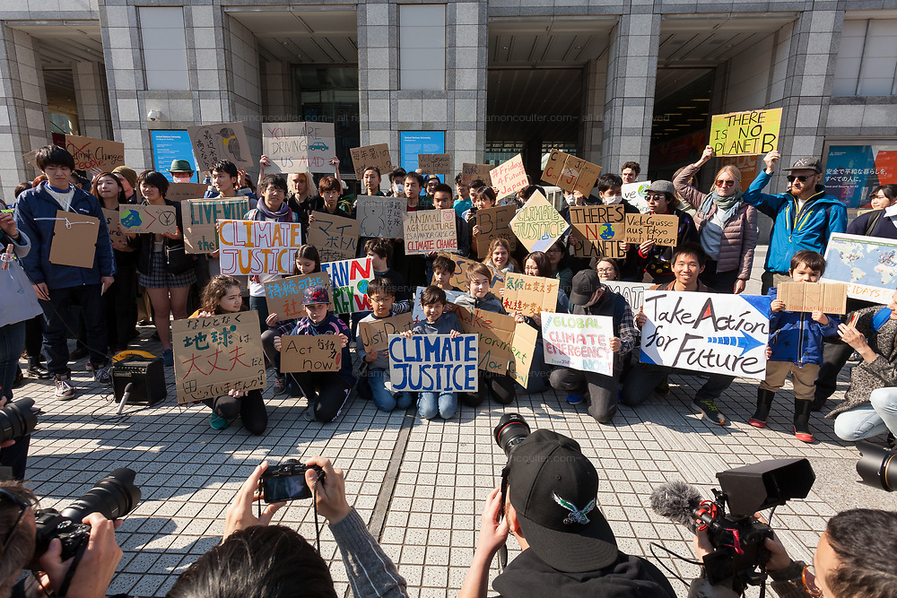 "Media photograph and film young Japanese people taking part in the Global Strike for Future at the United Nations University, Shibuya, Tokyo, Japan.Friday March 15th 2019. Part of a global day of action in 98 countries and nearly 2,000 cities; this was Japan's second Fridays for Future event, known as ""School strikes"", and took place from 2pm to 4pm with activists and students holding signs demanding leaders, internationally and nationally, take measures to reduce ecologically damaging activities. The movement was started in 2018 by Swedish schoolgirl, Greta Thunberg, who began striking from her lessons when she realised that adult leaders were doing nothing to ensure there would be the future she was studying for."