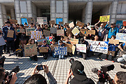 """Media photograph and film young Japanese people taking part in the Global Strike for Future at the United Nations University, Shibuya, Tokyo, Japan.Friday March 15th 2019. Part of a global day of action in 98 countries and nearly 2,000 cities; this was Japan's second Fridays for Future event, known as """"School strikes"""", and took place from 2pm to 4pm with activists and students holding signs demanding leaders, internationally and nationally, take measures to reduce ecologically damaging activities. The movement was started in 2018 by Swedish schoolgirl, Greta Thunberg, who began striking from her lessons when she realised that adult leaders were doing nothing to ensure there would be the future she was studying for."""