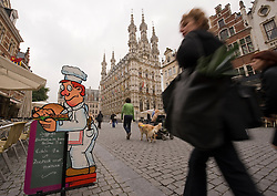 Pedestrians and cyclists make their way through the Grote Markt and past the ornate city hall building, in Leuven, Belgium, Saturday, Sept. 13, 2008.  (Photo © Jock Fistick)