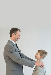Father talking to son with hands on his shoulder, smiling