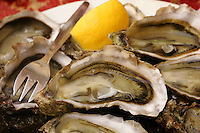 .Oysters served on the weekends at the Paris Wine Bar, Baron Rouge..a perfect example of a symbiotic business relationship, oyster farmer Bernard Delis arrives every weekend from November to April with a truck load of his oysters from the Bay of Archachon, near Bordeaux..He opens them outside the bar and they are served with lemon, and bread and butter, a traditional method..The bar is always jammed with plates of oysters on every conceivable surface, including the hoods, trunks,  and rooves of the parked cars..
