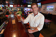"""Lloyd Cueto, part owner of Pitchers Sports Pub & Pizzeria in downtown Belleville, hoists a draft beer after Gov. Rauner signed a bill bringing """"Happy Hour"""" back to bars throughout Illinois."""