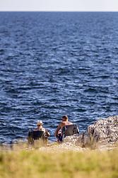 THEMENBILD - zwei Männer in Sonnenstühlen sonnen sich auf den Klippen der Adria, aufgenommen am 26. Juni 2018 in Pula, Kroatien // two men in chairs sunbathing on the cliffs of the Adriatic, Pula, Croatia on 2018/06/26. EXPA Pictures © 2018, PhotoCredit: EXPA/ JFK