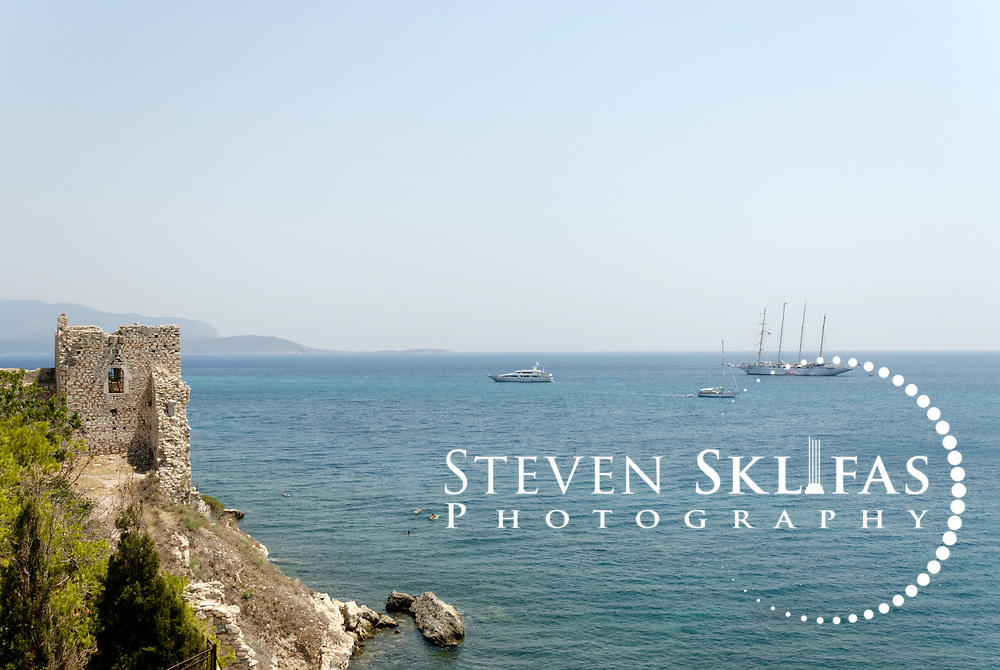 Greece. Samos. Boats ships sailing the Aegean Sea near the ruins of the old Byzantine castle in the town of Pythagoreio. The Kastro was reinforced with new buildings in order to serve the needs of the Struggle for independence and is named after Lykourgos Logothetis, the local chieftain who organised a decisive naval victory over the Turks on August 6 1824. The town's cemetery is beside the Kastro as is the church of Metamorfosis, built to celebrate the victory. Also in the Kastro grounds are ruins of two opulent villas of the Hellenistic period (2nd BC), Roman galleries and the remains of a 5th century Christian Basilica.  The Kastro is in the pretty seaside town of Pythagorio which is a UNESCO Cultural World Heritage Site and is named after the great philosopher Pythaogaras who was born here in 580 BC.