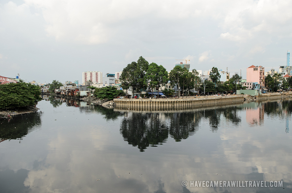 The calm water surface of the Saigon River reflects the makeshift houses on the water's edge in Ho Chi Minh City (Saigon), Vietnam.