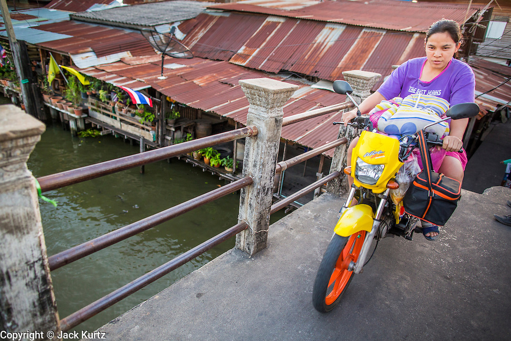 13 JANUARY 2013 - BANGKOK, THAILAND: A woman rides her motor scooter across Khlong Bang Luang in Bangkok. The Bang Luang neighborhood lines Khlong (Canal) Bang Luang in the Thonburi section of Bangkok on the west side of Chao Phraya River. It was established in the late 18th Century by King Taksin the Great after the Burmese sacked the Siamese capital of Ayutthaya. The neighborhood, like most of Thonburi, is relatively undeveloped and still criss crossed by the canals which once made Bangkok famous. It's now a popular day trip from central Bangkok and offers a glimpse into what the city used to be like.    PHOTO BY JACK KURTZ