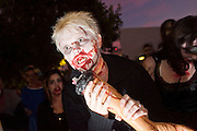 """Oct. 30, 2009 -- PHOENIX, AZ: Zombie SARAH LADAS """"dines on human flesh"""" (actually a theatre prop) during the Zombie Walk in Phoenix Friday. About 200 people participated in the first """"Zombie Walk"""" in Phoenix, AZ, Friday night. The Zombies walked through downtown Phoenix """"attacking"""" willing victims and mixing with folks going to the theatre and downtown sports venues.  Photo by Jack Kurtz"""