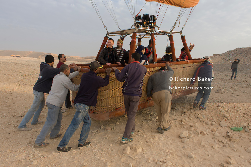 The ground crew of a hot air balloon operation push the basket towards more even ground after its landing on to wasteground in a West Bank village of the modern city of Luxor, Nile Valley, Egypt.