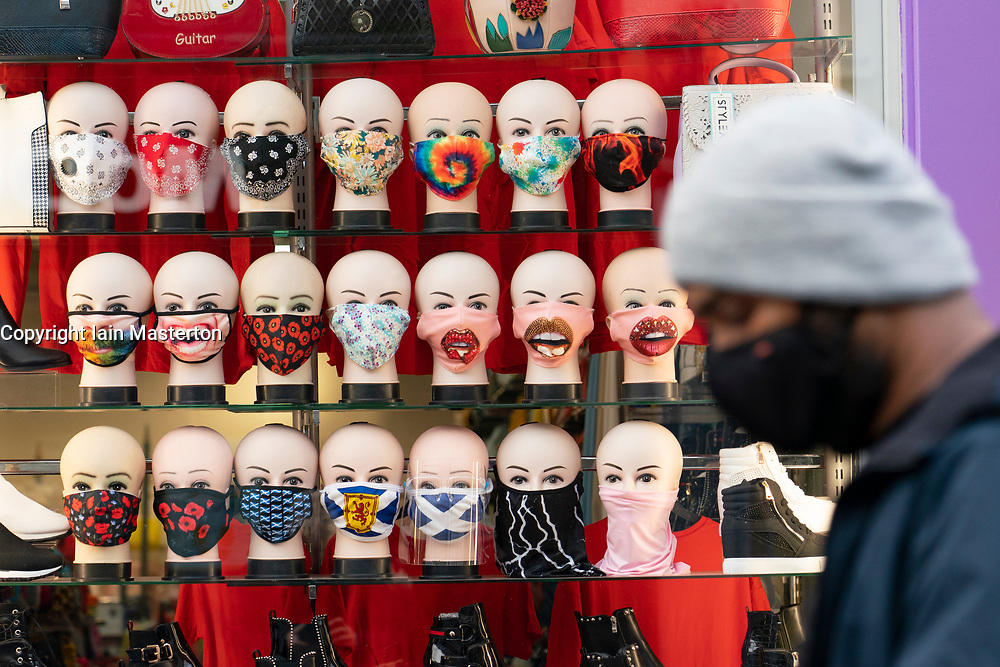 Glasgow, Scotland, UK. 26 October 2020. View of Glasgow city centre on weekday during circuit breaker lockdown with bars and restaurants closed. Pictured; Man in facemsrk walks past shop selling facemasks . Iain Masterton/Alamy Live News
