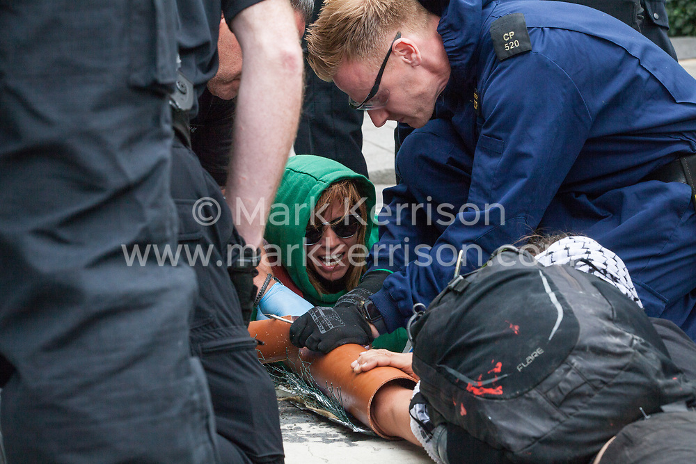 London, UK. 2 September, 2019. Police officers try to remove activists who had locked on using an arm tube to block a road outside ExCel London on the first day of week-long protests against DSEI 2019, the world's largest arms fair.