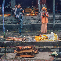 A Hindu ascentic blesses a corpse before its cremation at  Pashupatinath Temple in Kathmandu, Nepal, 1986.