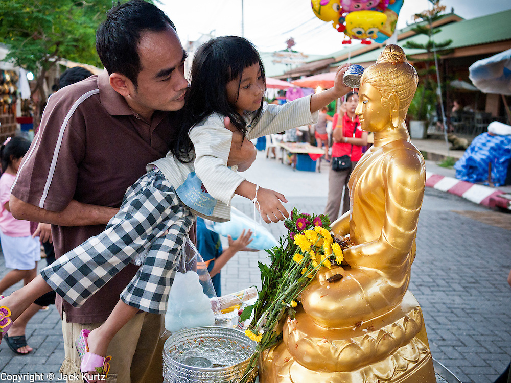 """26 JUNE 2011 - CHIANG MAI, THAILAND:  A man helps his daughter bathe a statue of the Buddha to """"make merit"""" in the """"Walking Street"""" market in Chiang Mai, Thailand. The Walking Street market is a weekly, Sunday night, market along Ratchadamnoen Street in Chiang Mai.   PHOTO BY JACK KURTZ"""