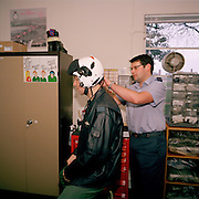 Survival Equippers (squippers) of the Red Arrows, Britain's RAF aerobatic team, fits a guest's helmet in the supplies office.