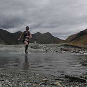 Runner Cate Parry crosses Moke Creek on the Ben Lomond High Country Station during the Pure South Shotover Moonlight Mountain Marathon and trail runs. Moke Lake, Queenstown, New Zealand. 4th February 2012. Photo Tim Clayton