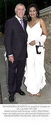 MR & MRS BRUCE FORSYTH at a party in London on 4th July 2001.OPY 332