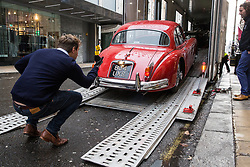 London, UK. 29th November, 2018. Auctioneers Bonhams move a 1959 Jaguar XK150 'S' 3.4 Litre Coupé in preparation for an auction of historic and high-performance racing and road cars. Highlights include a Le Mans class-winning Jaguar XJ220C driven by David Coulthard (£2,200,000-2,800,000), a Lister Jaguar Knobbly (£2,200,000-2,800,000) and a 1958 BMW 507 owned by its designer, as well as Ferraris, Aston Martins, Bentleys, Porsches and Jaguars. Bonhams, founded in 1793, is one of the world's largest and most renowned auctioneers of fine art and antiques, motor cars and jewellery.