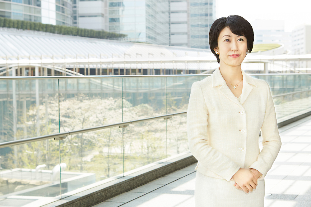 Portrait photograph of a Japanese businesswoman in the Shinagawa business district in Tokyo Japan, futuristic looking architecture in the background