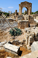 Tyre, Lebanon - September 1, 2010: Roman ruins at the Al-Bass Archaeological Site in Tyre, Lebanon. Towering in the background is the monumental archway, built in the second century AD. In the foreground is a sarcophagi.